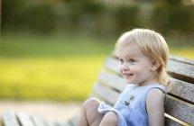 Portrait de petite fille blonde souriante assise sur le banc du parc — Photo de stock