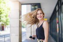 Retrato de joven sonriente lanzando su pelo - foto de stock