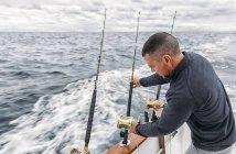Pescatore a bordo di un peschereccio che adegua le canne da pesca sul Mar Cantabrico, Asturie, Spagna — Foto stock