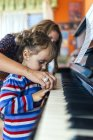 Женщина и маленькая девочка вместе играют на пианино — стоковое фото