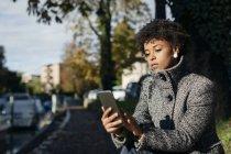 Beautiful black woman using smartphone, outdoor in autumn — Stock Photo