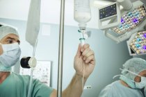 Operating room nurse checking the drip of an IV bag during surgery — Stock Photo