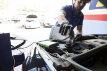 Mechanic refilling oil in car at workshop — Stock Photo