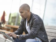 Young man sitting on bench using digital tablet — Stock Photo