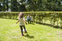 Father and daughter playing football in park — Stock Photo