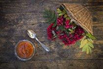 Upturned basket with rowan berries and glass of fresh rowan berry jam on dark wood — Stock Photo