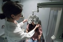 Ophthalmologist adjusting an optometrist phoropter, for eye calibration of a patient — Stock Photo