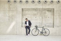 Businesssman with bicycle at concrete wall reading document — Stock Photo
