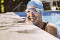 Triatleta feminina sorrindo feliz na borda da piscina — Fotografia de Stock