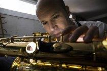 Instrumento fabricante desmontagem saxofone durante a reparação — Fotografia de Stock