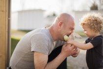 Padre e hija pequeña jugando con peluche - foto de stock