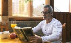 Homme assis à la table du petit déjeuner lecture d'un livre — Photo de stock