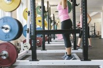 Young Woman lifting barbell in a power rack — Stock Photo
