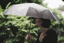 Женщина с зонтиком в дождливый день — стоковое фото