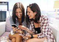 Glücklich Freundinnen Blick auf Telefon und lachend auf Terrasse — Stockfoto