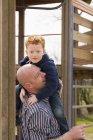 Батько несучи сина на майданчику — стокове фото