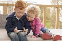 Мальчик и девочка смотрят на мобильный телефон — стоковое фото