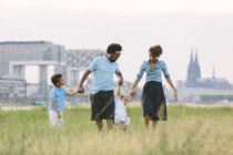 Heureuse famille afro-américaine de quatre marche dans un champ — Photo de stock