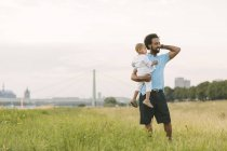 Happy african american father carrying his son in field — Stock Photo