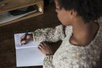 Jeune femme au bureau écrit dans un cahier — Photo de stock