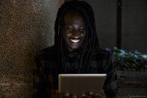 Giovane uomo di colore utilizzando la tavoletta digitale nel buio — Foto stock