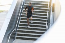 Young active man running downstairs — Stock Photo