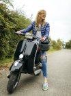 Сміючись блондин жінка, сидячи на чорний моторолер — стокове фото