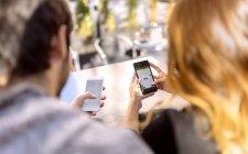 Rückansicht eines jungen Paares, das nebeneinander sitzt und seine Smartphones benutzt — Stockfoto
