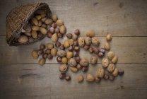 Cesta de mimbre, nueces, almendras y avellanas sobre madera - foto de stock