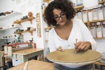Femme décorant une assiette dans un atelier de céramique — Photo de stock