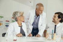 Trois scientifiques parlant dans le laboratoire moderne — Photo de stock
