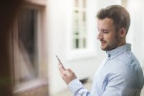 Young man looking at cell phone behind windowpane — Stock Photo