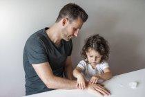 Дочка кріплення штукатурка на батьківську руку — стокове фото