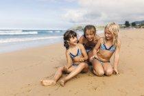 Испания, Коломбо, три девушки сидят на пляже, веселятся — стоковое фото