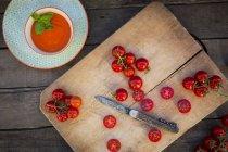 Cuenco de sopa de crema de tomate y tabla de cortar con tomates enteros y en rodajas - foto de stock