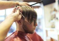 Barbiere taglio capelli di cliente maschile in negozio di barbiere — Foto stock