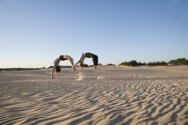 Акробат пара, выполняя сальто sychronous — стоковое фото