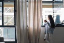 Mujer joven con taza de café mirando por la ventana abierta - foto de stock