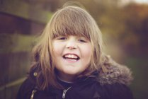 Portrait of girl in winter jacket laughing outdoors — Stock Photo