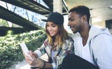 Улыбающаяся молодая пара смотрит на смартфон — стоковое фото