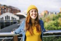 Ritratto di giovane donna sorridente che indossa un cappello di lana giallo che sporge la lingua — Foto stock