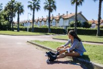 Espagne, Gijon, adolescente assise sur le trottoir attachant ses patins à roulettes — Photo de stock