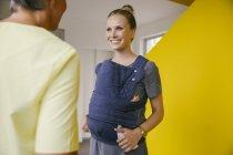 Junge Mutter mit Baby-Fördermaschine im Gespräch mit Frau im Flur — Stockfoto