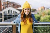 Ritratto di giovane donna sorridente con cappello e vestito di lana gialli — Foto stock