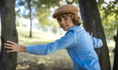 Portrait of blond boy wearing cap standing between two trees — Stock Photo