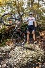 Горный велосипедист с велосипедом в лесу — стоковое фото