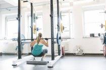 Donna che fa squat con bilanciere in un rack di potenza — Foto stock