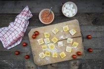 Raviolis caseros con tomate, mozzarella y salsa - foto de stock