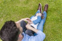 Father tickling daughter on meadow in park — Stock Photo