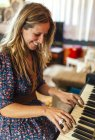 Femme souriante, jouer du piano — Photo de stock